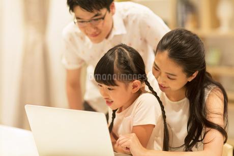 椅子に座ってパソコンを見る家族の写真素材 [FYI02968679]