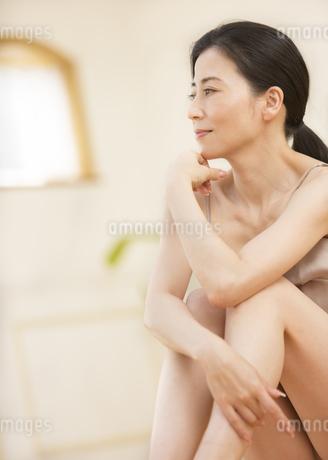 座って遠くを見つめる女性の横顔の写真素材 [FYI02968680]