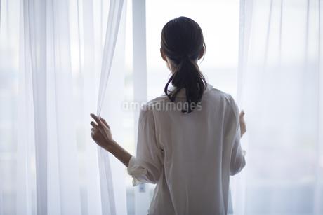 窓の外を見つめる女性の後ろ姿の写真素材 [FYI02968684]