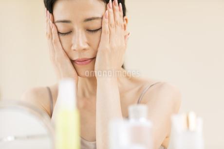 頬に両手を添えて目を瞑る女性の写真素材 [FYI02968690]