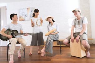 室内で楽器を持って演奏する男女の写真素材 [FYI02968692]