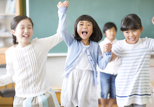 黒板の前で手を取り合って喜ぶ女の子たちの写真素材 [FYI02968694]