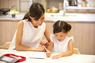 子供の勉強を見る母親の写真素材 [FYI02968697]