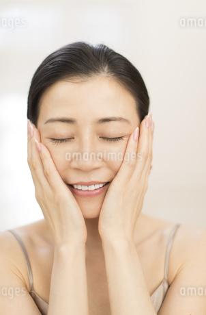 頬に両手を添えて目を瞑る女性の写真素材 [FYI02968701]