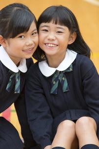 体育館で座って微笑む小学生の女の子2人の写真素材 [FYI02968702]