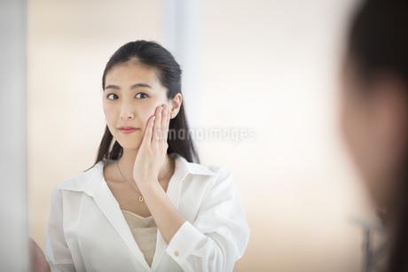 鏡の前で肌のチェックをする女性の写真素材 [FYI02968711]