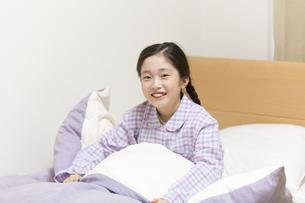 ベッドの上で微笑む女の子の写真素材 [FYI02968720]