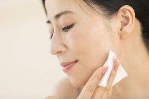 頬にコットンをあてスキンケアをする女性の写真素材 [FYI02968721]
