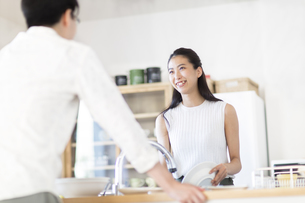キッチンで食器を洗いながら男性と話す女性の写真素材 [FYI02968722]