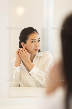 鏡の前でピアスを身につける女性の写真素材 [FYI02968730]