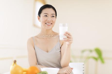 牛乳を手に微笑む女性の写真素材 [FYI02968733]