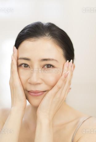 頬に両手を添える女性の写真素材 [FYI02968734]