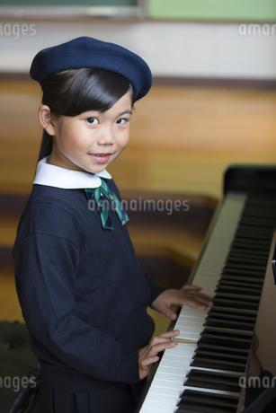 音楽室でピアノを演奏する女の子の写真素材 [FYI02968735]
