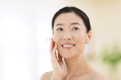 頬に片手を添えて微笑む女性の写真素材 [FYI02968736]