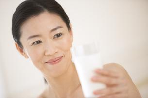 牛乳を手に微笑む女性の写真素材 [FYI02968739]