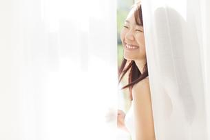 カーテン越しで笑う女性の写真素材 [FYI02968742]
