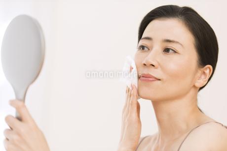 頬にコットンをあてスキンケアをする女性の写真素材 [FYI02968743]