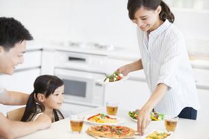 家族に食事を用意する母親の写真素材 [FYI02968749]