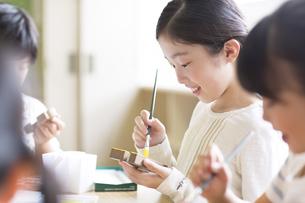 絵具の筆で色を塗る女の子の横顔の写真素材 [FYI02968755]
