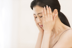 頬に両手を添えて目を瞑る女性の写真素材 [FYI02968756]