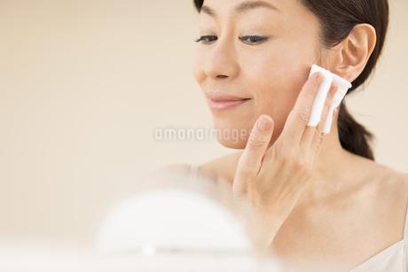 頬にコットンをあてスキンケアをする女性の写真素材 [FYI02968761]