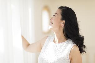 カーテンを開ける女性の写真素材 [FYI02968763]