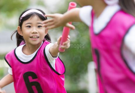 リレーのバトンを渡す女の子の写真素材 [FYI02968766]