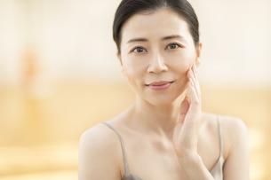 頬に片手を添えて微笑む女性の写真素材 [FYI02968767]