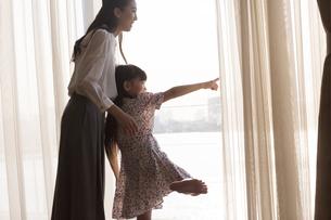 窓の外を眺める親子の写真素材 [FYI02968768]