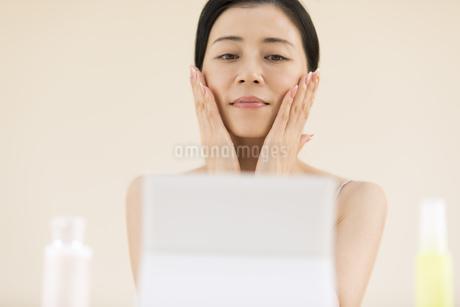 鏡の前でスキンケアをする女性の写真素材 [FYI02968770]