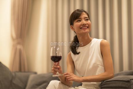 ソファーに座ってワインを手に遠くを眺める女性の写真素材 [FYI02968781]