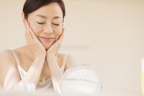 鏡の前でスキンケアをする女性の写真素材 [FYI02968786]