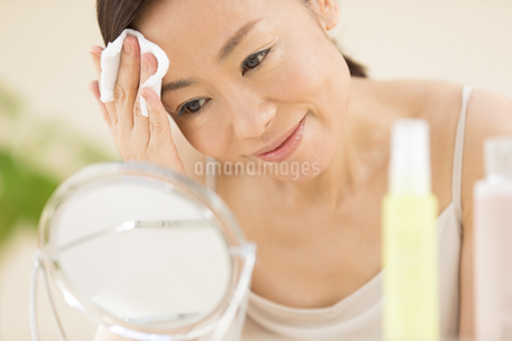 頬にコットンをあてスキンケアをする女性の写真素材 [FYI02968790]