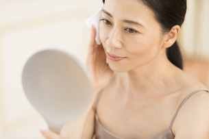 頬にコットンをあてスキンケアをする女性の写真素材 [FYI02968794]