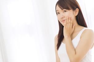 頬に片手を添える女性の写真素材 [FYI02968795]