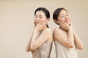 頬に両手を添えて目を瞑る2人の女性の写真素材 [FYI02968805]