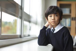 教室の窓際で肘をついて座る小学生の男の子の写真素材 [FYI02968814]