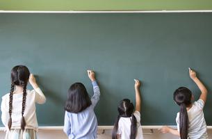 黒板に文字を書こうとする女の子4人の写真素材 [FYI02968815]