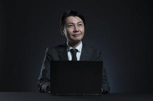 ノートPCの前で上を見上げるビジネス男性の写真素材 [FYI02968817]