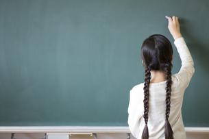 黒板に文字を書こうとする女の子の写真素材 [FYI02968820]
