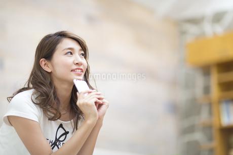 スマートフォンを持って遠くを眺める女性の写真素材 [FYI02968823]