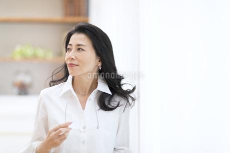 眼鏡を手に持って遠くを見つめる女性の写真素材 [FYI02968824]