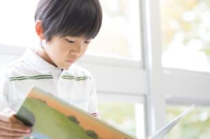教室の窓際で本を読む男の子の写真素材 [FYI02968825]
