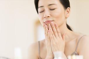 顎に両手を添えて目を瞑る女性の写真素材 [FYI02968833]