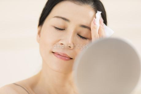 頬にコットンをあてスキンケアをする女性の写真素材 [FYI02968838]