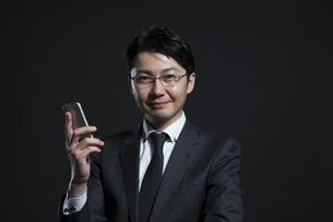スマートフォンを手に持つビジネス男性の写真素材 [FYI02968841]