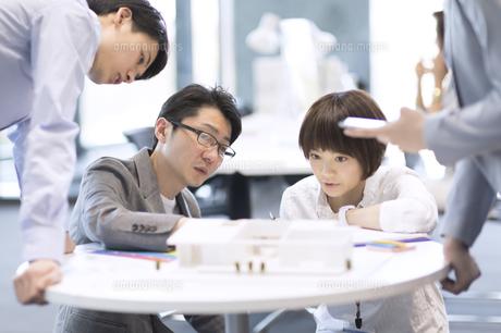 建築模型を使って打ち合せをするビジネス男女の写真素材 [FYI02968845]