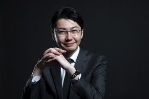 手を組み微笑むビジネス男性の写真素材 [FYI02968847]