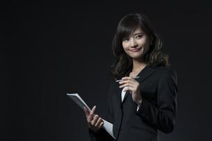 資料とペンを手に持ち微笑むビジネス女性の写真素材 [FYI02968849]