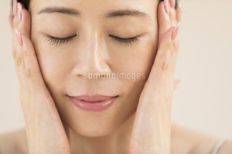 頬に両手を添えて目を瞑る女性の写真素材 [FYI02968851]